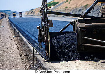 industrial pavement truck laying fresh asphalt on construction