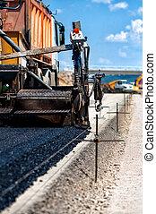 Industrial pavement truck or machine laying fresh bitumen...