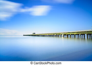 Industrial pier on the sea. Side view. Long exposure photography.