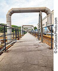 Industrial pipelines in loop on pipe bridge. Tanks field