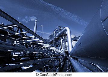 industrial pipelines on pipe-bridge against sky in blue tone...