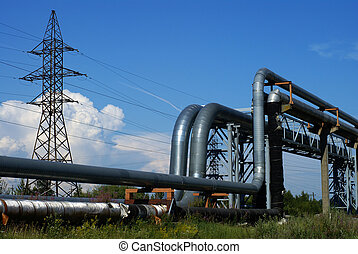 industrial pipelines on pipe-bridge and electric power lines against blue sky