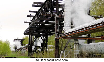 industrial pipelines on pipe-bridge from which emanate jets of steam