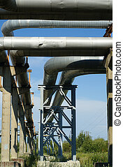 industrial pipelines on pipe-bridge against blue sky...