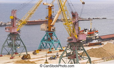 Industrial port area. Crane with bucket loads mortar sand in the truck.