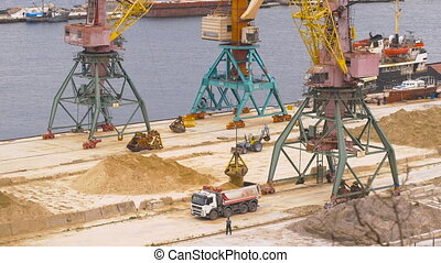Industrial port area. Crane with bucket loads mortar sand in...