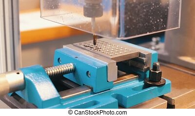 Industrial production. CNC machine carves a lot of holes -...