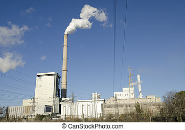 Industrial production site with a smoking chimney