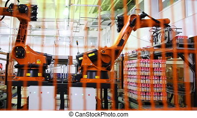 industrial robot puts yogurt packaging in neat rows on...