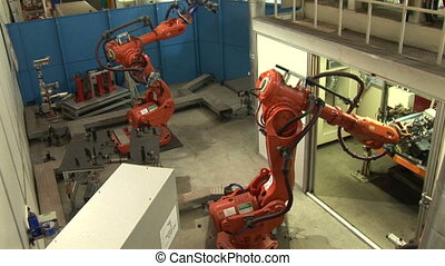 Images of two industrial robots assembling auto parts. Hydraulic operating robotic arms in a factory.