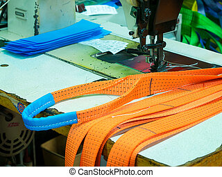 Industrial sewing machine sews a ratchet strap. Manufacture of textile slings and tie straps.