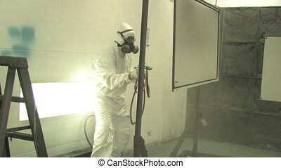 Industrial Spray Painting 2 - A man in a white jumpsuit and...