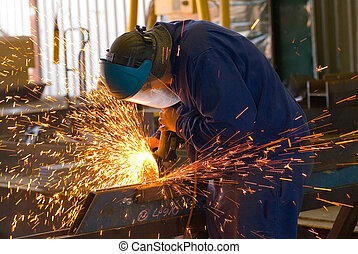 Industrial Steel Grinding - Sparks fly from a grinder in an...