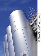 Industrial metallic tanks on blue sky