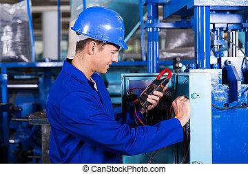 industrial technician examining control box with digital...