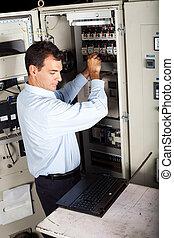 industrial technician repairing machine