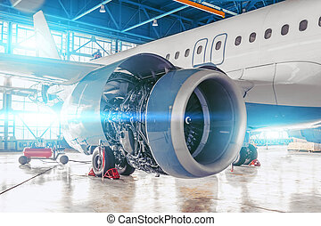 Industrial theme view. Repair and maintenance of aircraft jet engine with hood open on the wing.