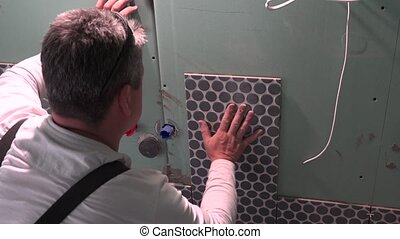 Industrial tiler builder worker working with floor tile laying in new flat house