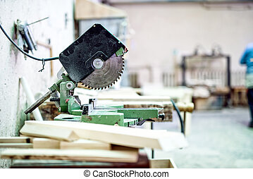 industrial tool in wood and metal factory, compound mitre saw with sharp, circular blade