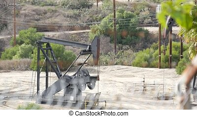 Industrial urban landscape. La Brea Inglewood in Los Angeles. Well pump jack operating behind the fence. Drilling rig extract crude oil. Oil mining machine with working piston. Oil and gas industry