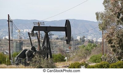 Industrial urban landscape. La Brea Inglewood in Los Angeles. Well pump jack operating behind the fence. Drilling rig extract crude oil. Oil mining machine with working piston. Oil and gas industry.