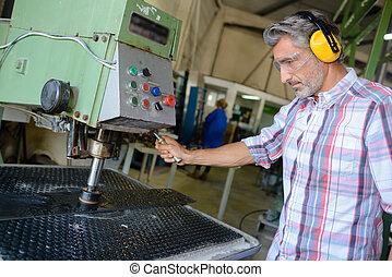 industrial, utilizar, orejeras, llevando, hombre, máquina