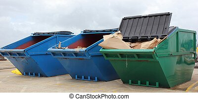 Large industrial waste skips coloured green and blue