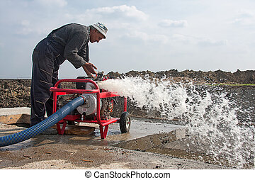 Industrial Water Pump - Worker puts into operation the...