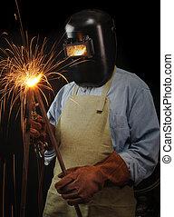 Industrial Welder - Welder torching a piece of steel against...