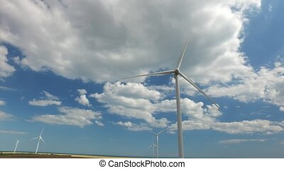 Industrial wind energy turbines the blue sky in thick white clouds. Aerial survey