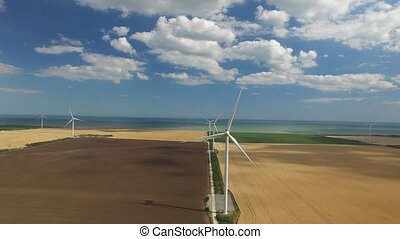 Industrial wind engine on a background of yellow green layer. Aerial survey