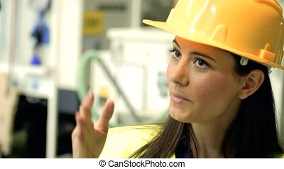 Industrial woman engineer standing in a factory, talking to unrecognizable man.
