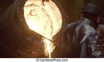 Industrial worker casting metal at metallurgical factory. Molding molten metal at industrial plant. Manufacturing iron products in heavy industry