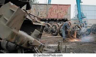Industrial worker cuts old metal wheels with a cutting torch...
