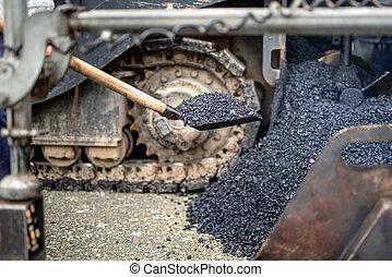 industrial worker, handyman using shovel for carrying asphalt at road construction works