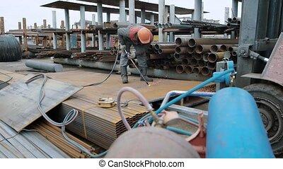Industrial worker in fireproof uniform cutting metal sheet...