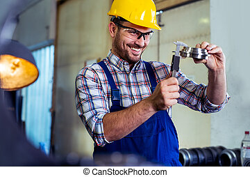 Industrial worker inspector measuring detail with Vernier Caliper