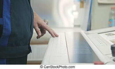 Industrial Worker. Man using industrial control panel of the Printing machine.