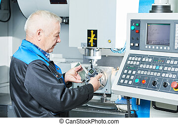 industrial worker measuring detail near cnc milling machine