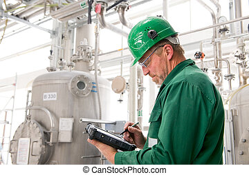 Middle aged industrial worker with notebook