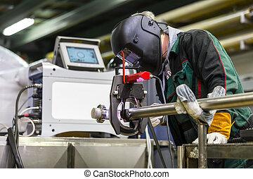 Industrial worker setting orbital welding machine. -...