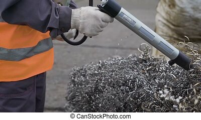 Industrial worker uses device to scan pile of silver spirals...