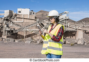 Industrial worker using tablet on construction site