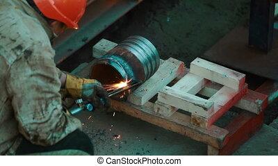 Industrial worker welding metal blank - Worker welding a...