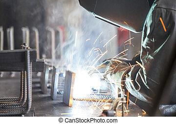 Industrial worker welding steel in the dark