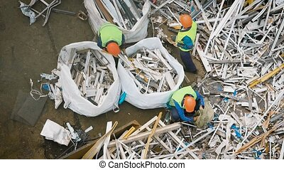 Industrial workers put piles of metal scraps in a bags for...