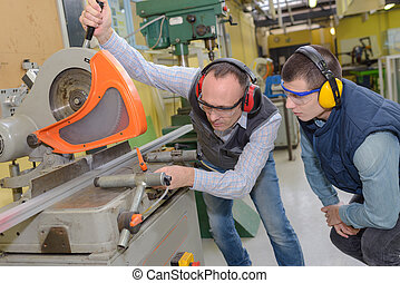 industrial workers using a metal cutter machine