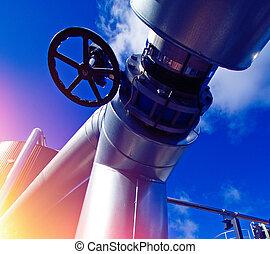 Industrial zone, Steel pipelines and tanks against blue sky