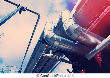 Industrial zone, Steel pipelines and tanks against blue sky...