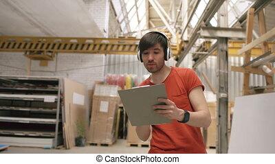 industriel, coup, écoute, work., danse, écouteurs, ouvrier, jeune, workplace., amusement, musique, chariot, avoir, entrepôt, pendant, homme, heureux